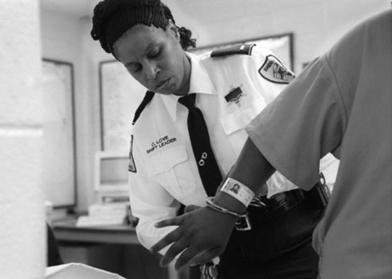 Leiutenant Love removes the handcuffs from an inmate so that she may make a phone call. Love spends much of her time in an office. Because she is simultaneously a shift leader for her platoon and the supervisor on duty, she handles any inmate infractions and makes most of the major decisions during her shift.